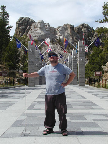 Tony standing in front of granite pillars flying the 56 flags. Mount Rushmore in the background.