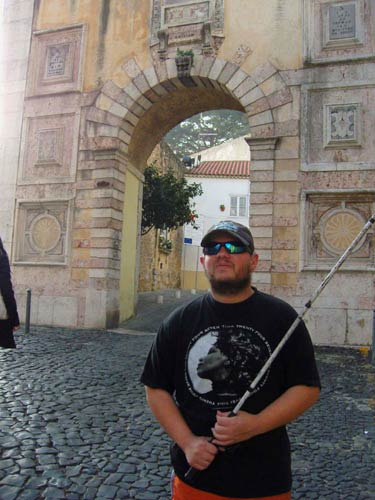 Tony in front of an archway leading into the castle