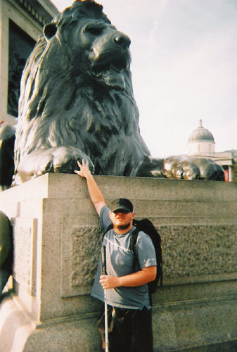 Tony in front of one of the lions in Trafalgar Square