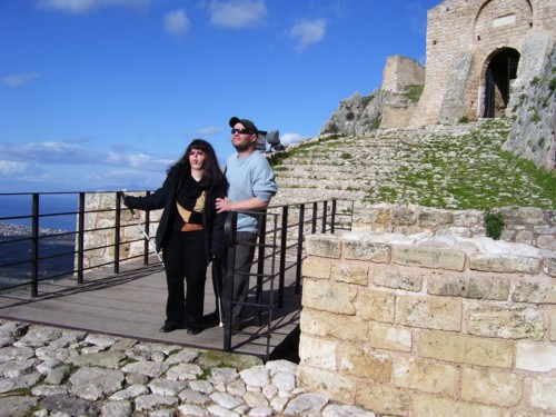 Tony and Tatiana on bridge in front of Korinth Castle with view of modern Korinth in background