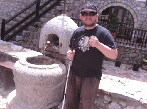Tony tasting freshwater from a drinking fountain in front of the monastery.