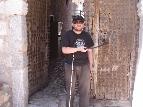 Tony by old wooden doors in the St. Naum monastery grounds.