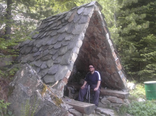 Tony sitting in a stone shelter.