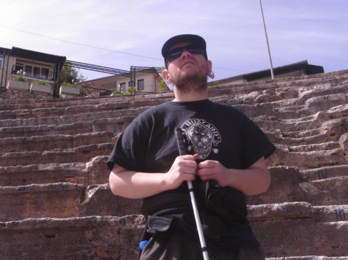 Tony inside the Anticki theatre. Rows of stone seating behind him.