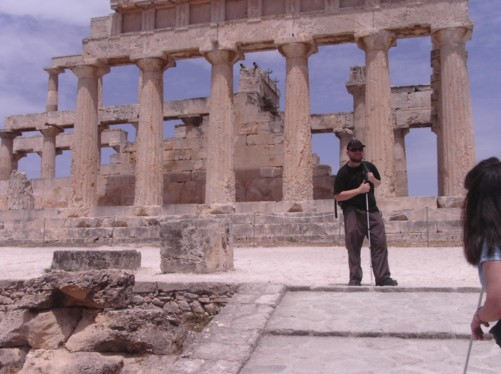 Tony at Athia Temple (APHAIIA or APHEAE). The temple stands on top of a hill lined with pine trees, about 4 km from the tourist port village of Agia Marina. The doric temple was built in the 5th century BC and 24 linestone columns remain as an example of its former structure. It was dedicated to Aphaia - a hunting nymph daughter of Zeus.