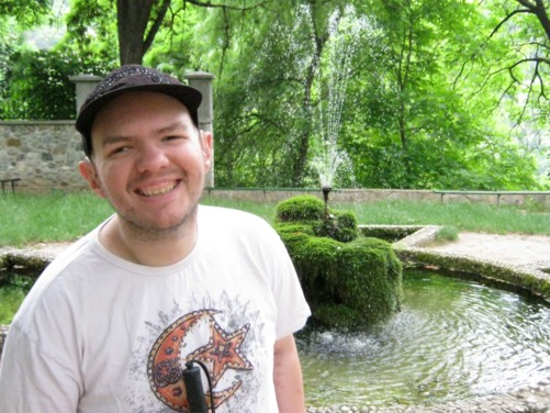 Tony by a pond and fountain in the grounds of Bachkovo Monastery.