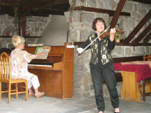 Two female musical entertainers in a restaurant, one playing the piano and the other the violin.