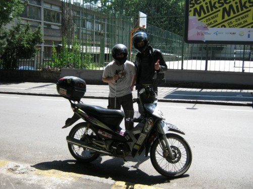 Tony standing behind a motorbike with Eion from France.