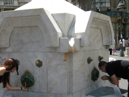 People drinking from fountain on Knez Mihailova Street. The fountain is located in front of the Centre for Spanish Culture.