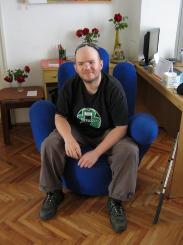 Tony in the grip of comfort! A strange handshaped chair at the Garden Hostel.