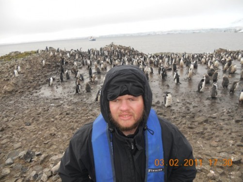 Tony on a rocky beach. A group of penguins behind, predominantly noisy Chinstrap penguins hurrying about.