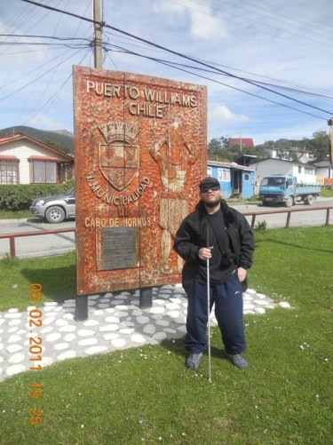 Tony by a welcome a sign in Puerto Williams town centre.