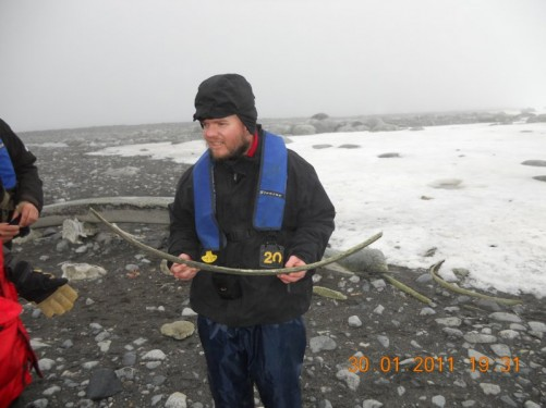Tony the discoverer, holding a long curved shaped rib bone from a whale. Whale bones are found scattered over the beach on Half Moon Island.