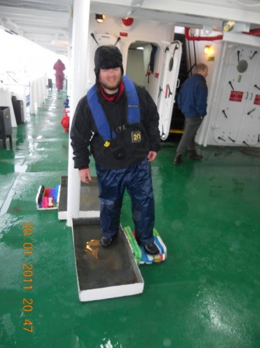 Tony cleaning off penguin poo from boots and trousers on the stern deck of the MV Ushuaia.