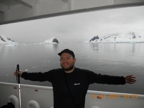 Tony on the deck as the ship passes along the Errera Channel. Away in the distance are rugged snow-covered islands.