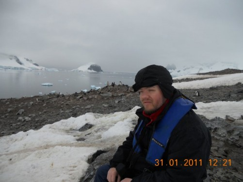 Tony sitting on a rock; view of the rocks and ice of the surrounding landscape.