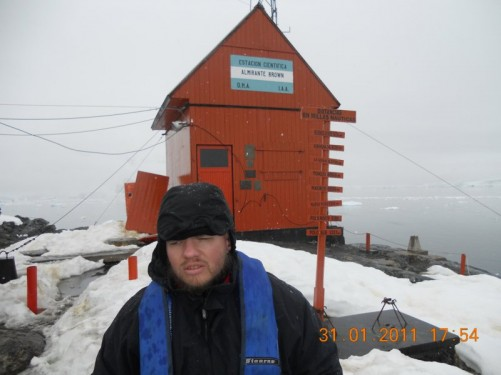 Tony outside a hut at Almirante Brown Antarctic Base. In front there is a sign post showing cities and their distances in nautical miles.