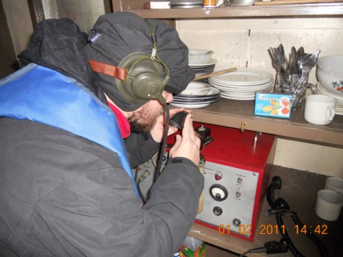 Tony wearing headphones while examining an old radio transceiver. Wordie House.