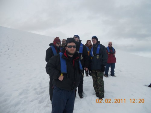 Tony with a group in a snow field. They are on a steep slope, heading up to a vantage point.