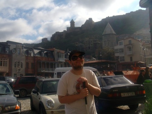Tony in a square filled with cars, in the old town, medieval Marikala District, Tbilisi.