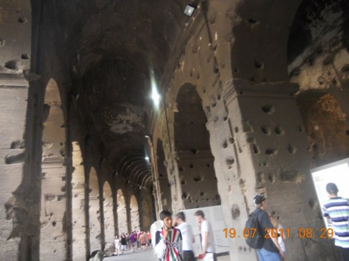 View along the outer walkway around the Colosseum with stone arches on both sides.