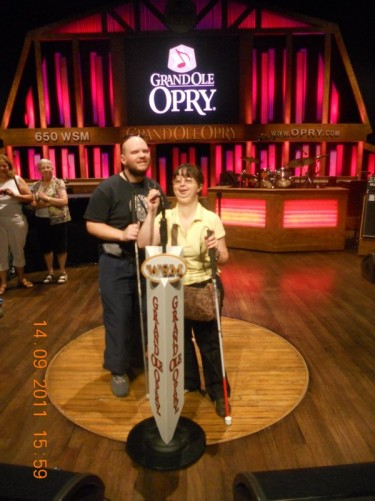 Tony, Tatiana standing in front of a microphone on the actual Grand Ole Opry stage.