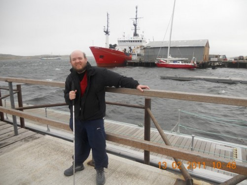 Tony at Stanley Harbour looking at the choppy South Atlantic with a boat in the background.