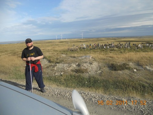 Tony stood on East Island's main road across the island, boot hill and wind mills in the distance. A few miles outside Stanley.