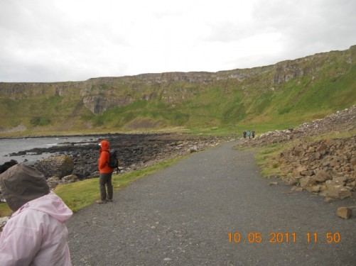 Wide footpath immediately above a rocky beach at Causeway Coast, solidified lava constructed cliffs in the distance.