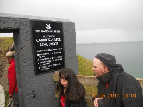 Tony, Tatiana by the 'Welcome to Carrick-a-Rede Rope Bridge' sign. Carrick-a-Rede Rope Bridge is a 30 foot, 20 metre long suspension bridge located near Ballintoy, County Antrim.