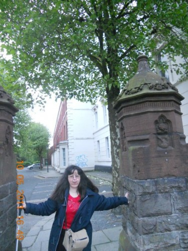 Tatiana stood between two stone columns, perhaps once used as gateposts. Near Queens University, Belfast. Taken during an evening walk around Belfast.