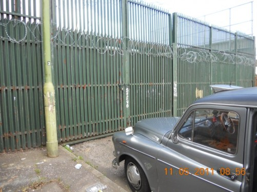 The taxi in front of an 18 foot, 5 metre high steel gate atopped with sharp spikes and barb wire. One of the barrier gates, part of the Peace Line.