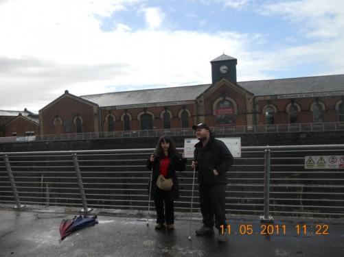 Tony, Tatiana stood by railings, behind is the Thompson Dry Dock from which the famous liner, RMS Titanic of White Star, constructed by Harland and Wolff, was built and launched.