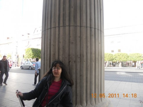 Tatiana leaning against one of the original columns, a bullet hole is just above her head, photo taken by Tony.