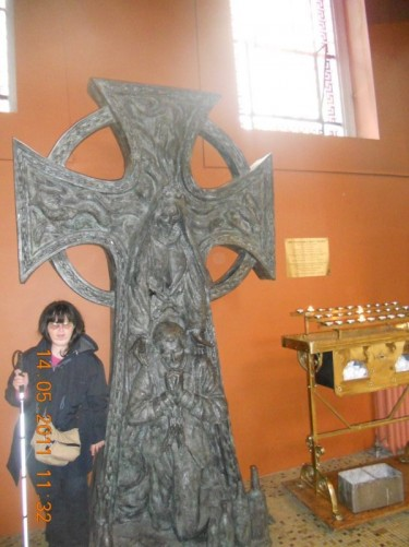 Tatiana beside a metal sculpture in the shape of a cross inside the cathedral.
