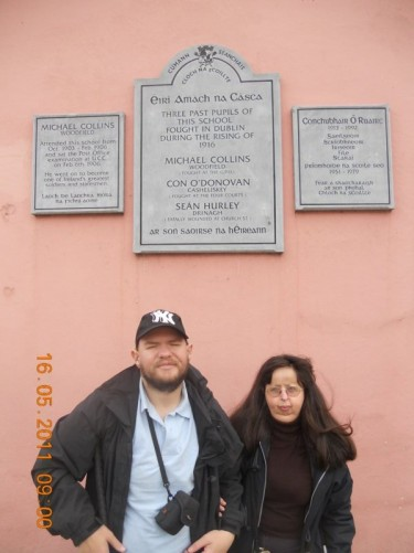 Tony, Tatiana in front of a wall and plaque which reads: 'Three past pupils of this school fought in Dublin during the rising of 1916. Michael Collins, Con O'Donovon, Sean Hurley.' Located in the small town of Clonakilty, West Cork.