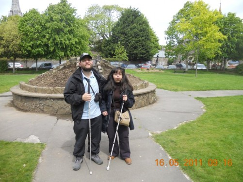 Tony, Tatiana in a park, Colman's Cathedral is visible, a circular monument behind.