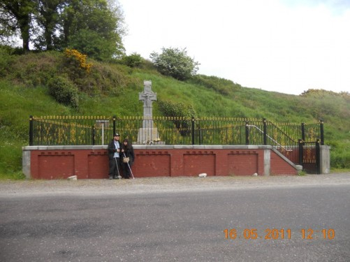 Tony, Tatiana in front of a stone cross surrounded by railings, a memorial to Michael Collins, situated at Beal na Blath.