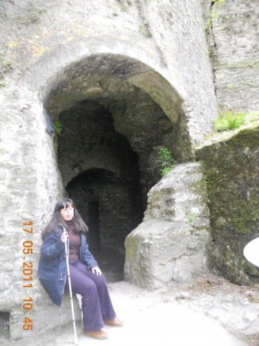 Tatiana outside an entrance of thick stone walls, possibly the castle dungeon, located at the lower part of the hill up to the main tower.
