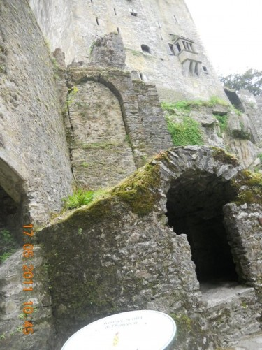 A view looking up at the thick stone castle walls.