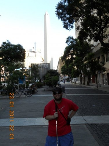 Tony in the commercial area of San Nicolas with the 67.5 metre high Obelisk of Buenos Aires in the background.