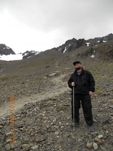 Tony on a higher level of the mountain trail. View up hill: little vegetation now, rocks and snow above.