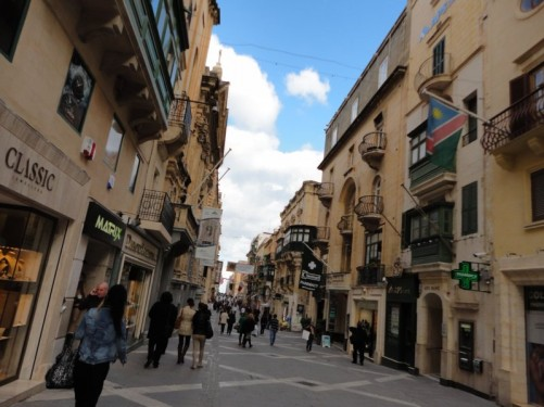 View along Republic Street (Triq ir-Repubblika, in Maltese). This is Valletta's main street, which runs straight down the middle of the city. It is lined with shops and is often crowded with people.
