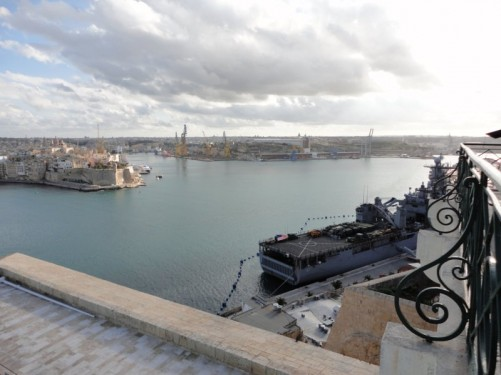 Looking down at a military frigate docked in the harbour.