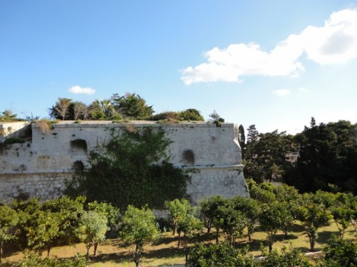 Part of the historic defensive wall around Mdina town with an area of park in front.