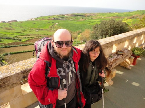 Tony and Tatiana with bags ready to leave on the hostel terrace. View of fields going downhill to cliffs and the sea below.