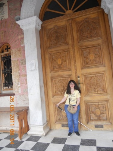 Tatiana in front of the cathedral's large carved-wood doorway.