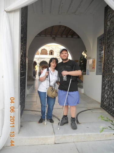 Tony and Tatiana standing in the outer doorway of the Church of Panagia Ekatontapiliani (Our Lady of 100 Gates). The church is located in the main square/plaza.