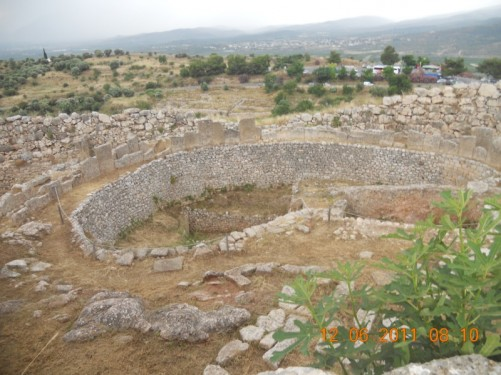 Mycenae. Remains of the palace, with substantial stone walls. The site is on a hillside.
