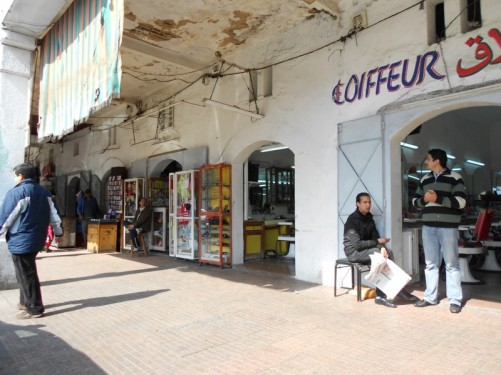 A row of shops, including a hairdressers immediately in front. A wide pavement. To provide shade, the buildings overhang the pavement supported by columns. The north end of Boulevard Mohammed V, one of the main avenues in Rabat
